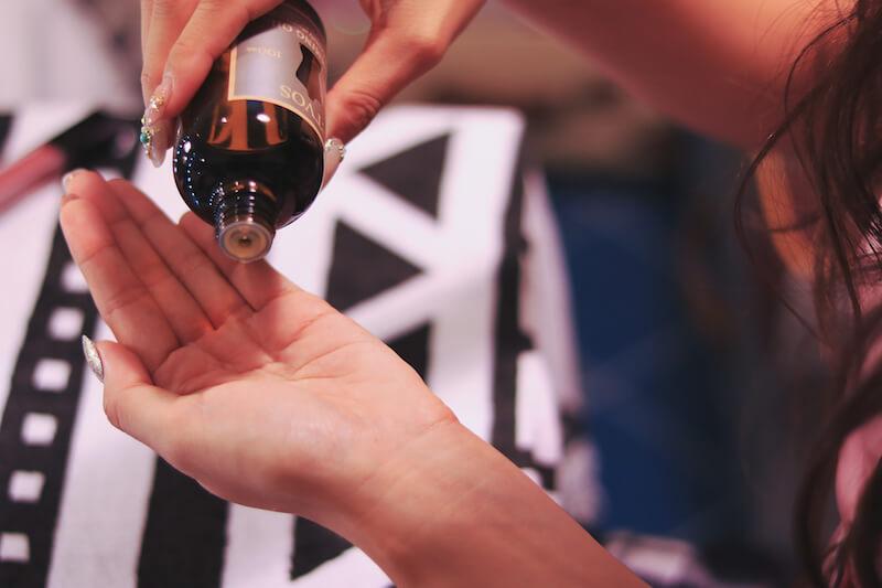 手に化粧水を垂らしている女性