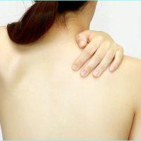 自分の綺麗な背中に手を回している女性の画像
