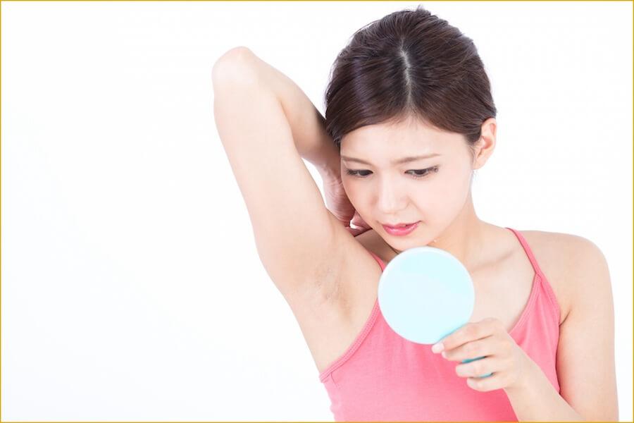 自分の脇の汚れ・くすみが気になり、手鏡で見ている女性の画像